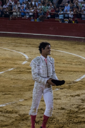 A matador walks around the stadium after a successful fight